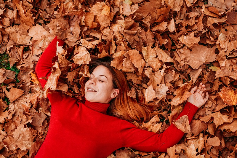 Young woman lying on the autumn leaves in the park photo