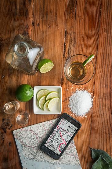 Tequila drink beverage alcohol map travel salt wood limes bottle photo