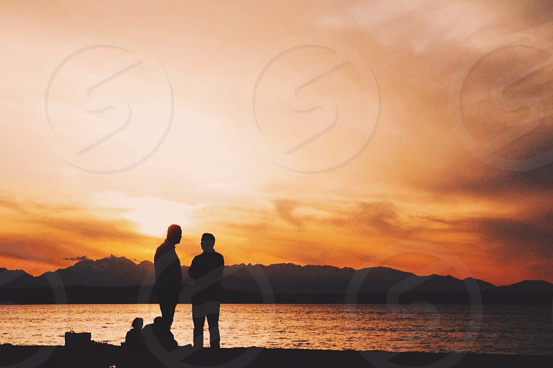 two people standing near ocean watching sunset photo