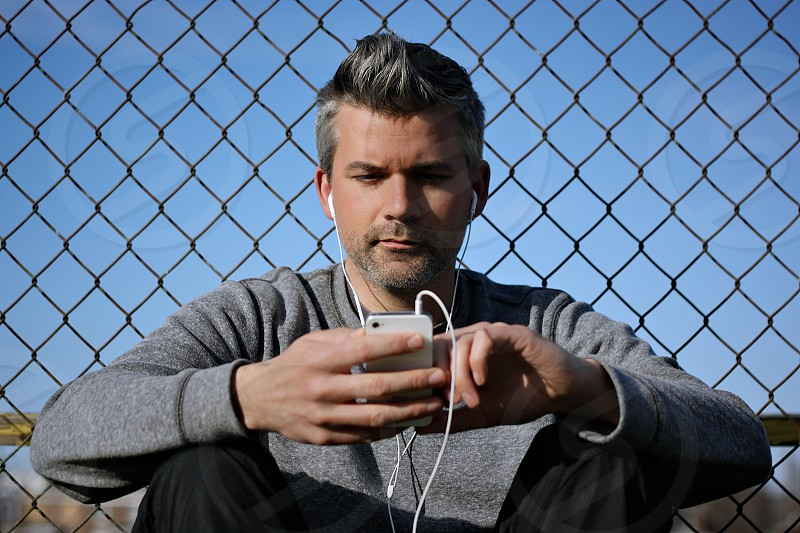 man wearing grey sweater looking at ipod photo