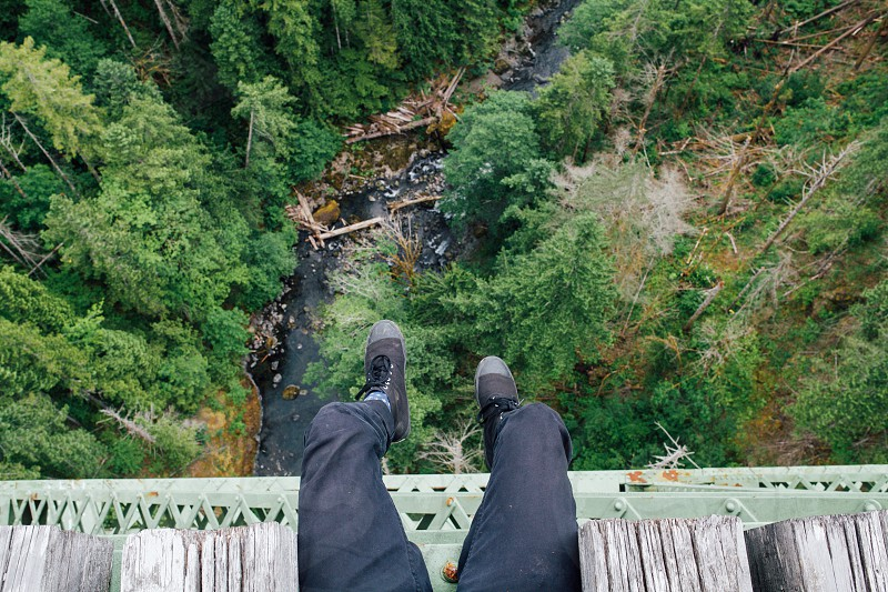 person in black pants wearing black lace up sneakers sitting on brown and green bridge over rushing river lined with green trees during daytime photo