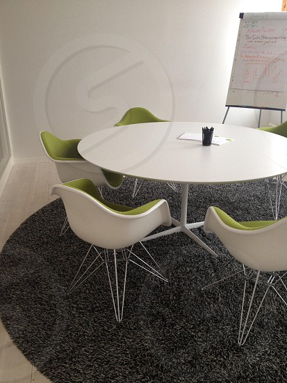 white table with white chairs green lining on top of grey round rug photo