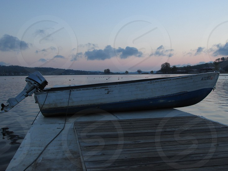 wooden boat with motor parked on wooden pier photo