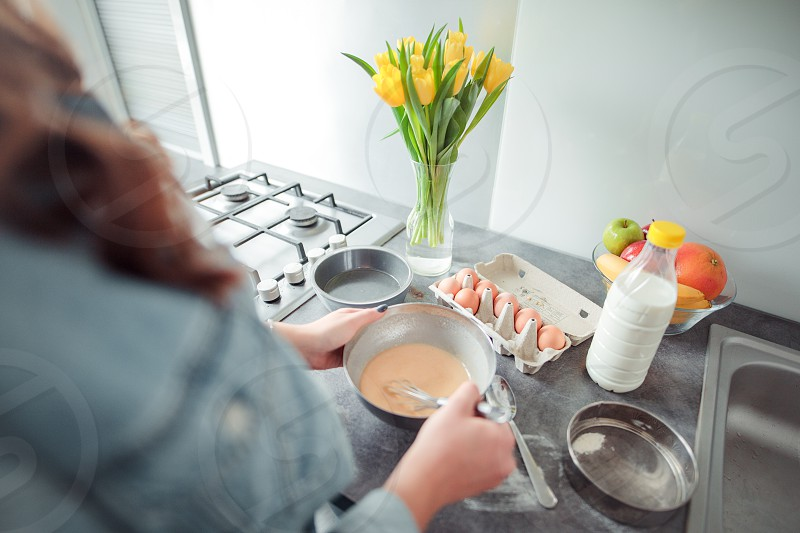 Girl cooking pancakes in the kitchen home with flowers eggs fruits on the table. photo