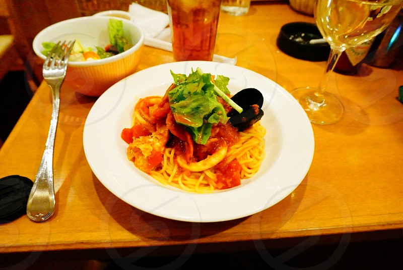 plate of noodles with red sauce and salad photo