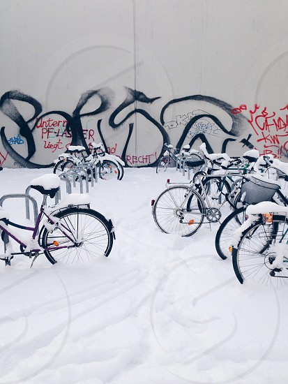 rows of snow-covered bicycles on snow-covered street by graffiti'd gray wall photo