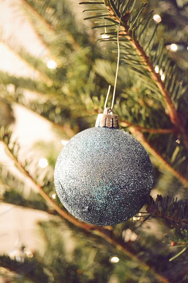 gray glittered bauble on a christmas tree\ photo