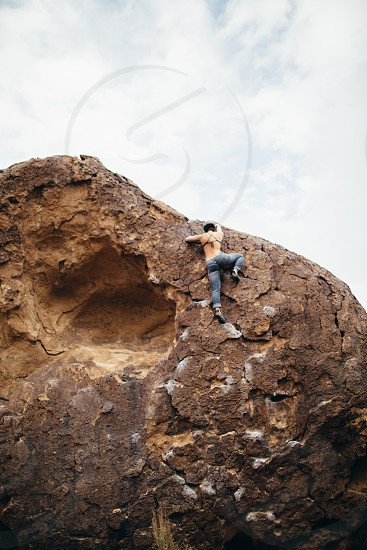 person wearing blue denim jeans climbing the rock face below white clouds and blue sky during daytime photo