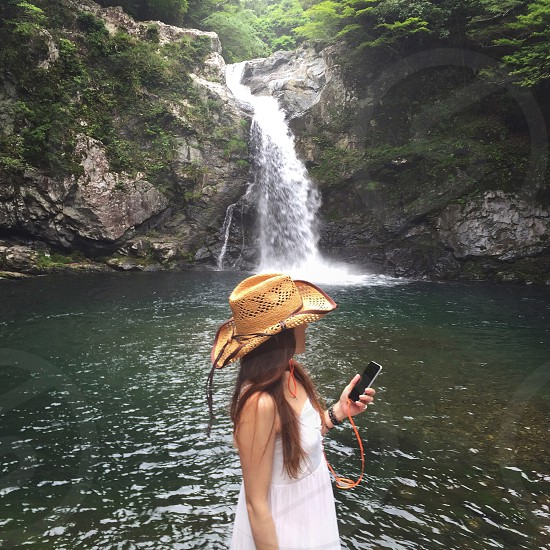 woman in white tube top dress and brown woven hat using a black smartphone by waterfalls photo