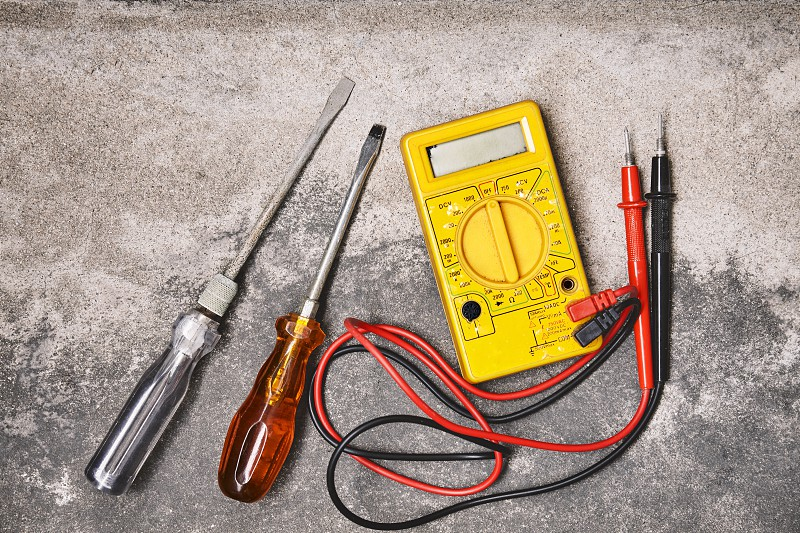 DIY home electricity working tools concepts Old screwdrivers and electricity voltage multi-meter on dusty cement background photo