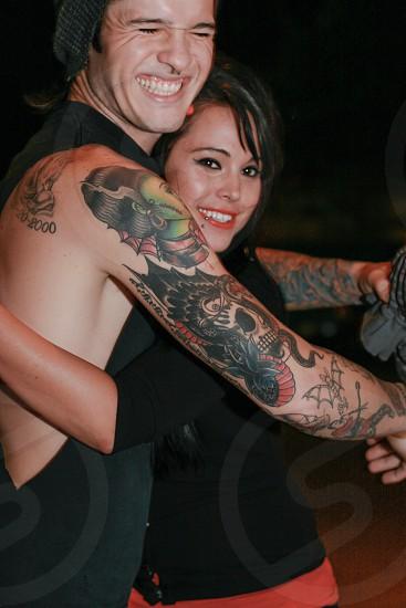 man in black tank top hugging woman in black shirt photo