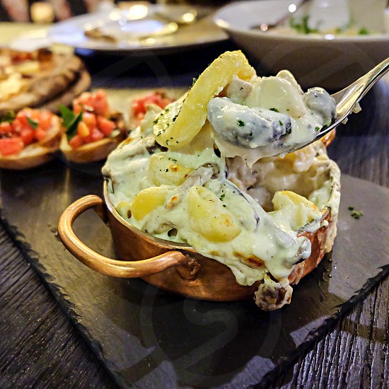 cheesy baked dish in copper pot on table photo