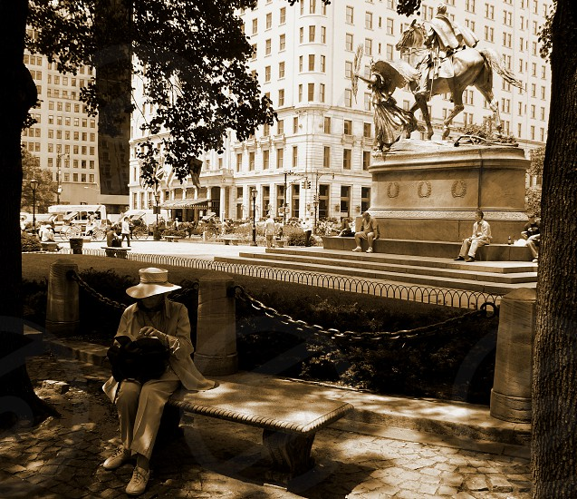 In sepia a woman sits on a bench near a statue in the foreground. 5th Avenue and the Plaza Hotel is in the background. photo