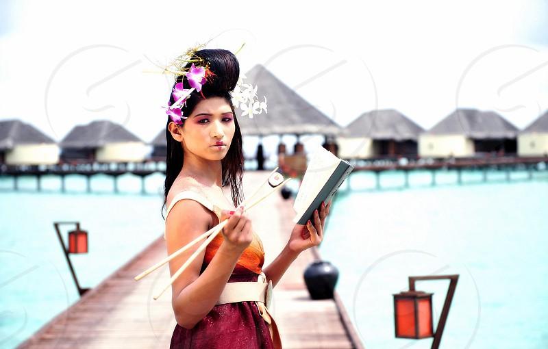woman holding a chopsticks on a dock photo