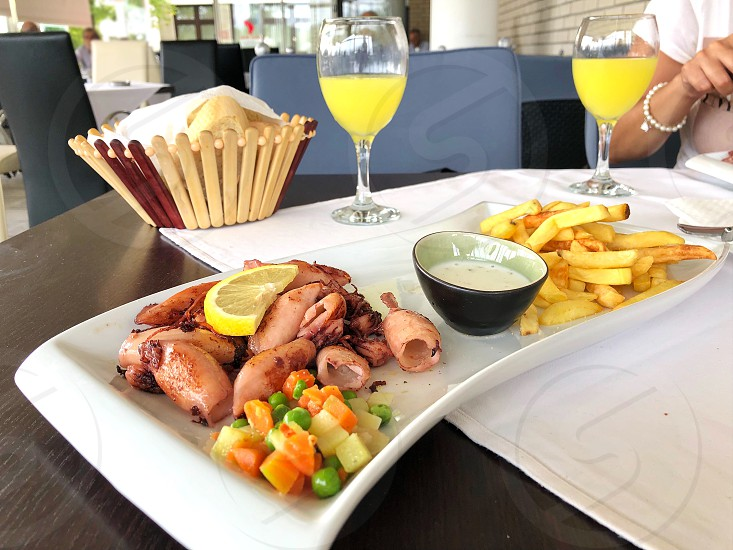 Closeup of squids with French fries and vegetables served in a restaurant photo