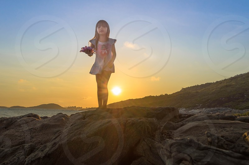 girl standing on rock sunset photo photo