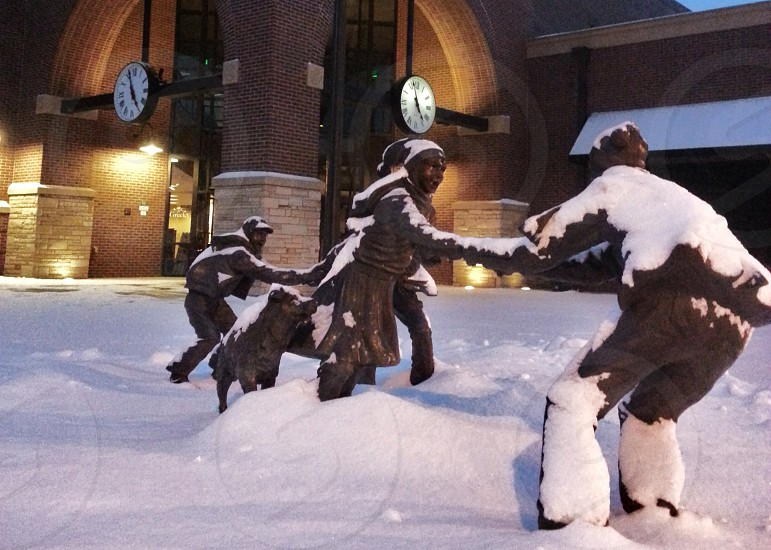 gray statues of people playing in snow photo