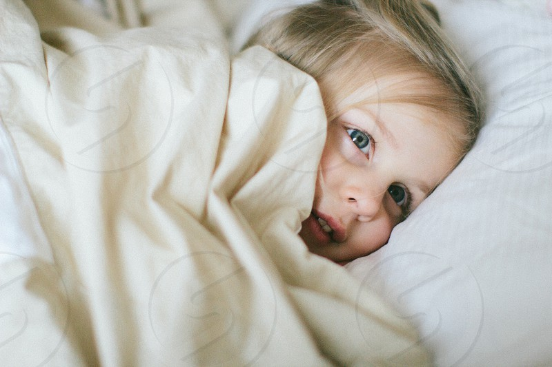 girl in white fabric blanket photo