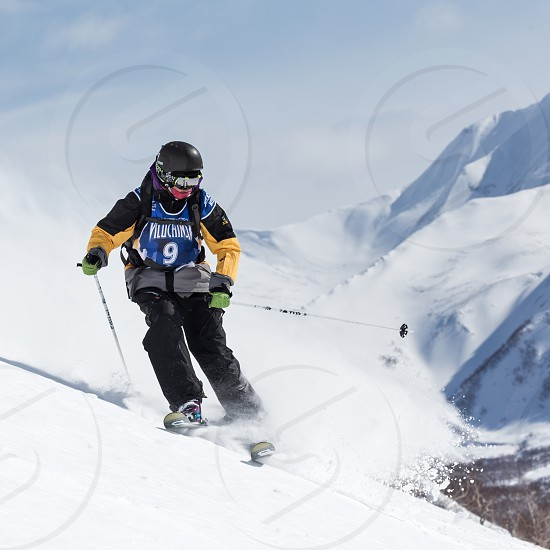 """KAMCHATKA RUSSIA - MARCH 9 2014: Skier rides steep mountains. Competitions freeride snowboarders and skiers """"Kamchatka Freeride Open Cup"""". Russia Far East Kamchatka Peninsula. photo"""