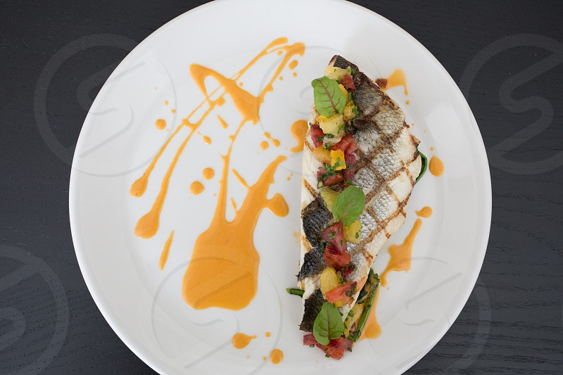 black white cooked fish with red green toppings and yellow sauce on the side placed on white round plate photo