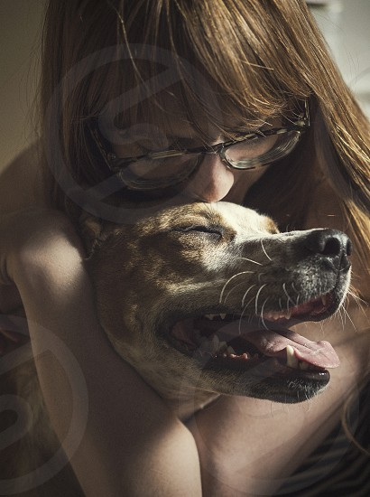 A woman hugging her pet dog.  photo