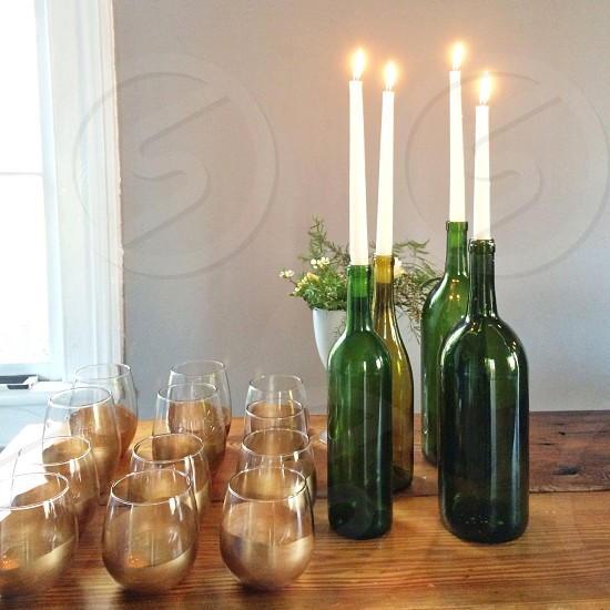 green glass wine bottle and clear whisky tumbler on table photo