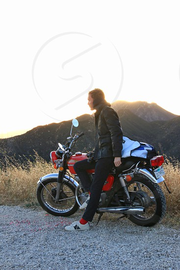 man in black leather motorcycle jacket  leaning on black and red standard motorcycle during sunrise photo