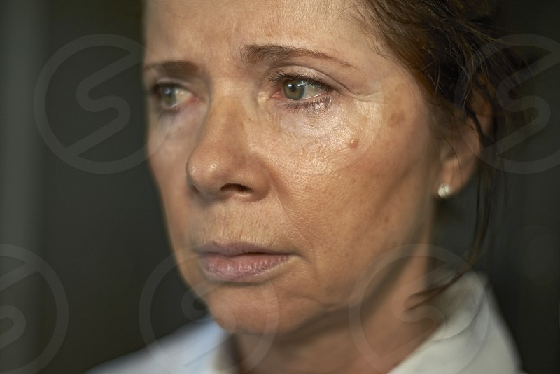 Portrait of an elderly retired woman looking upset and lonely with teary eyes photo