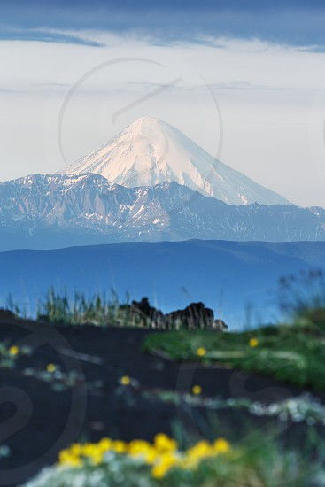 Summer volcanic landscape of Kamchatka Peninsula: view of active Kronotsky Volcano (Kronotskaya Sopka) in clear weather sunny day. Eurasia Russian Federation Far East Kamchatka Region. photo