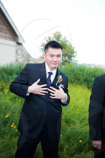 man in black suit with calla lily flower photo