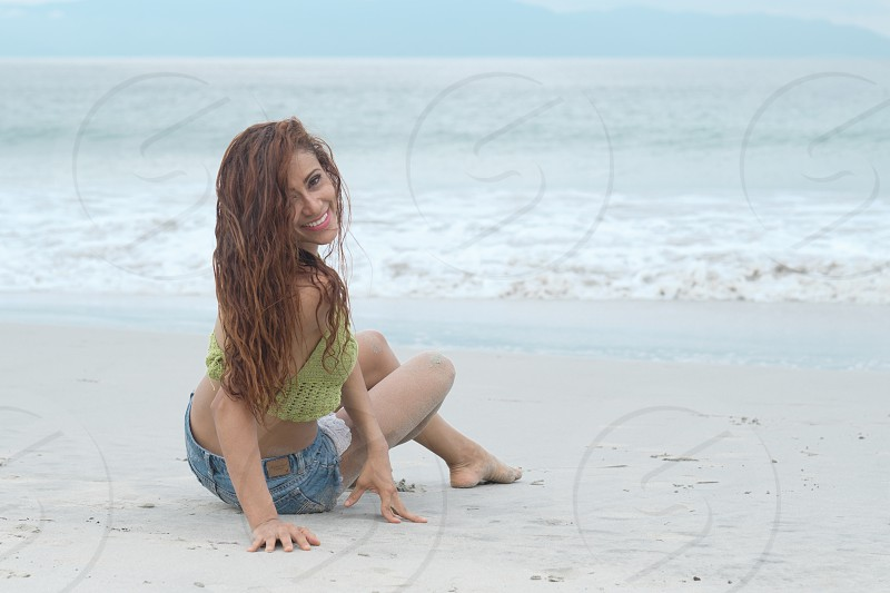 Barefoot woman sitting in sand at beach smiling while turning her body back photo