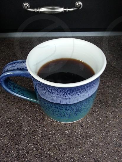 Coffee in hand-crafted mug photo