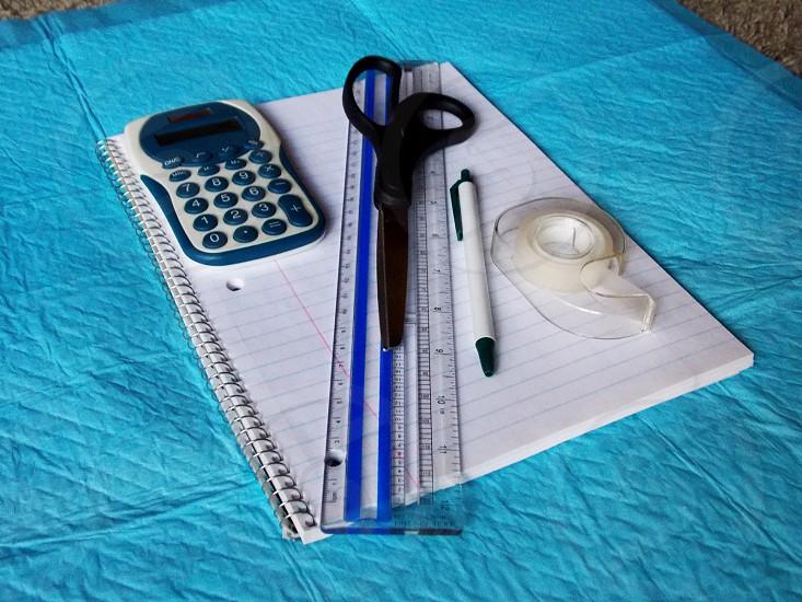 blue and white calculator plastic ruler scissors click pen tape dispenser on notebook photo
