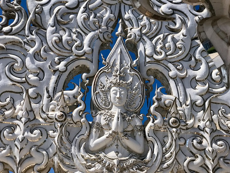 Outdoor day landscape horizontal colour Wat Rong Khun The White Temple Chiang Rai Thailand Thai Kingdom of Thailand travel tourism tourist wanderlust summer summertime temple Buddhist Buddhism spiritual pure holy dragon monster carved ornate elaborate art modern sculpture sculpted east eastern hands silver mirror mosaic magical mythical blue sky Buddha contrast screen photo