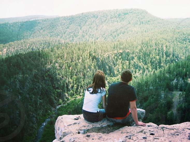 boy and girl sitting on cliff photo