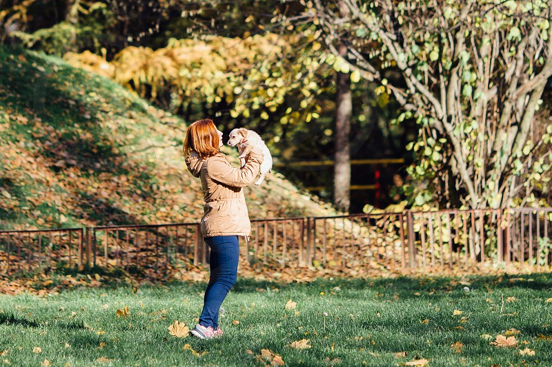Girl with her pet walking on the park autumn background photo