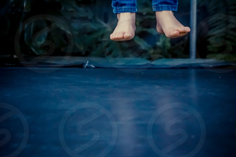 Legs floating in the air after jumping on the trampoline. photo