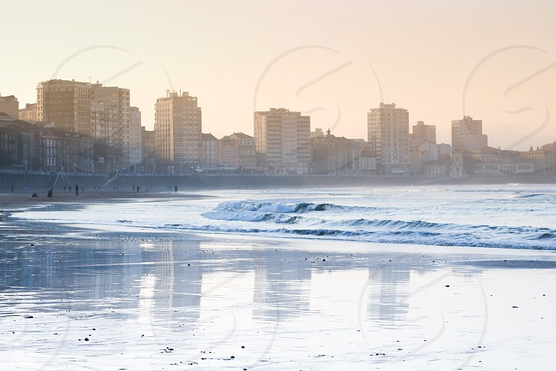 Cityscape of Gijón reflected on the beach of San Lorenzo at sunset. photo