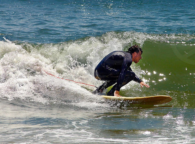 Man surfing a wave . Summer day at the beach. Sun sand salty water wet suit surfboard  photo