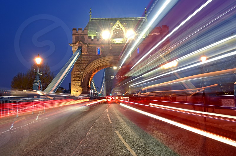 Vehicles pass over Tower Bridge across the River Thames in London UK. photo
