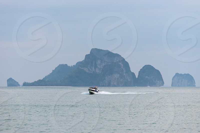 One speedboat in the sea water against the large cliff on background returns back photo