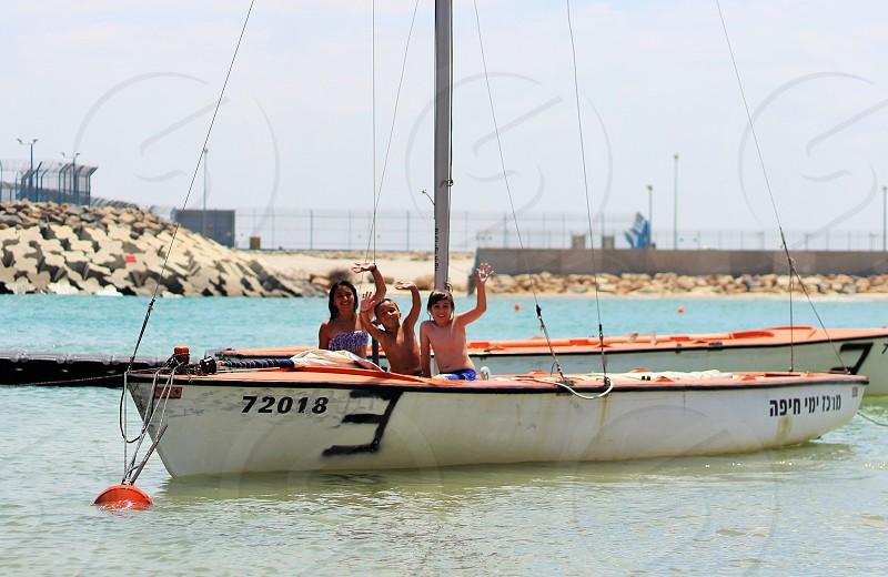 Kids on white sailing boat photo