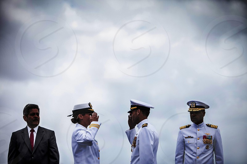 A male and female navy officers / lieutenants solute one another during a ceremony under a dark cloudy sky. photo