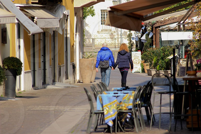 man in blue hoodie holding hands while walking with woman in black hoodie on street during daytime photo