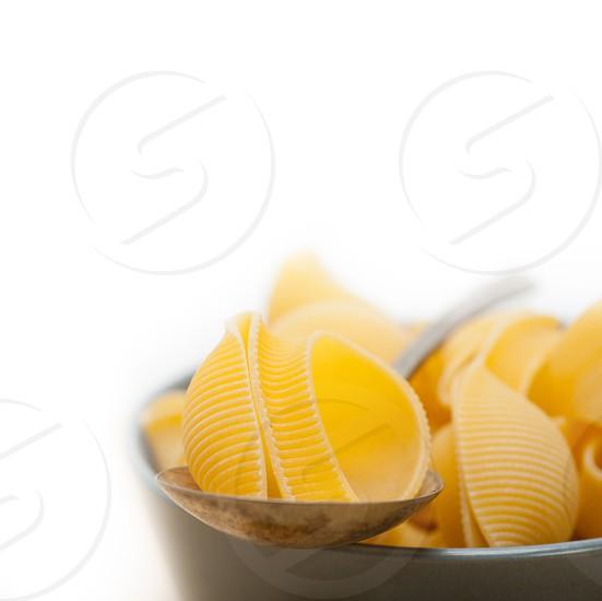 raw Italian snail lumaconi pasta on a blue bowl over rustic table macro photo