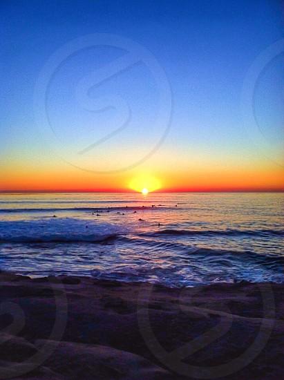 sunset over blue ocean photo