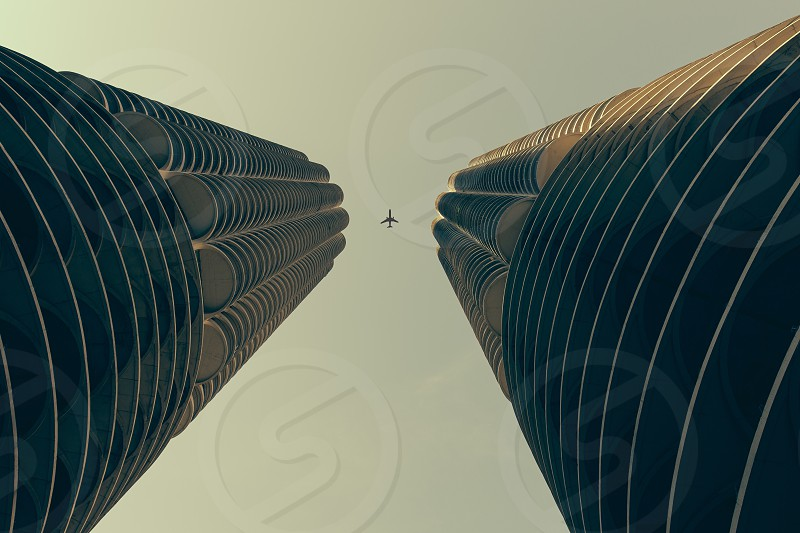 low angle photography of high rise 2 tower with plane flying in middle photo