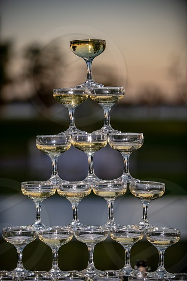 Champagne glasses stacked up in a pyramid photo
