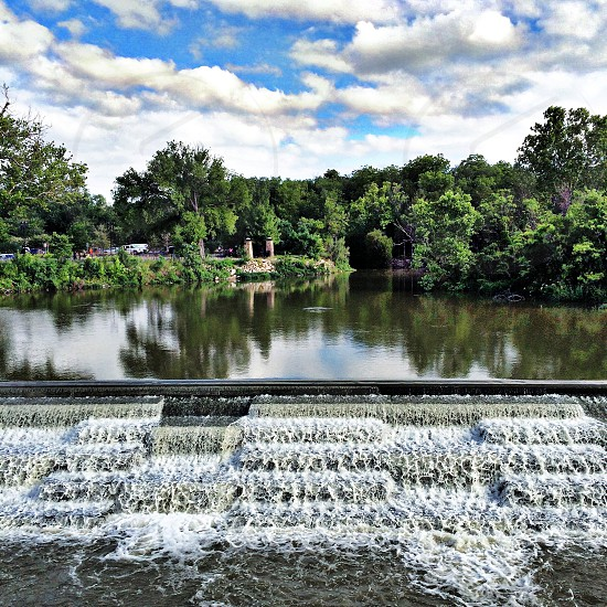 White Rock Spillway in Dallas Texas. Water flowing with lots of trees in the background on a sunny day.  photo
