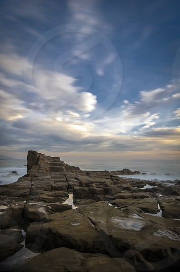 promontory rock formation sunset clouds peaceful zen stairs cloud movement calm ocean sea perch high tower land and sea long exposure reflection tower time  photo